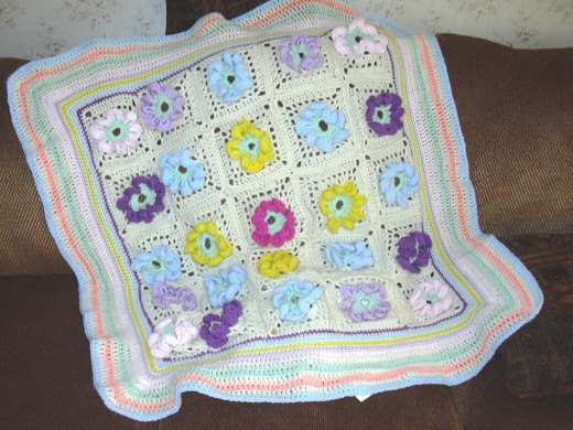 Crochet blanket with striped border.