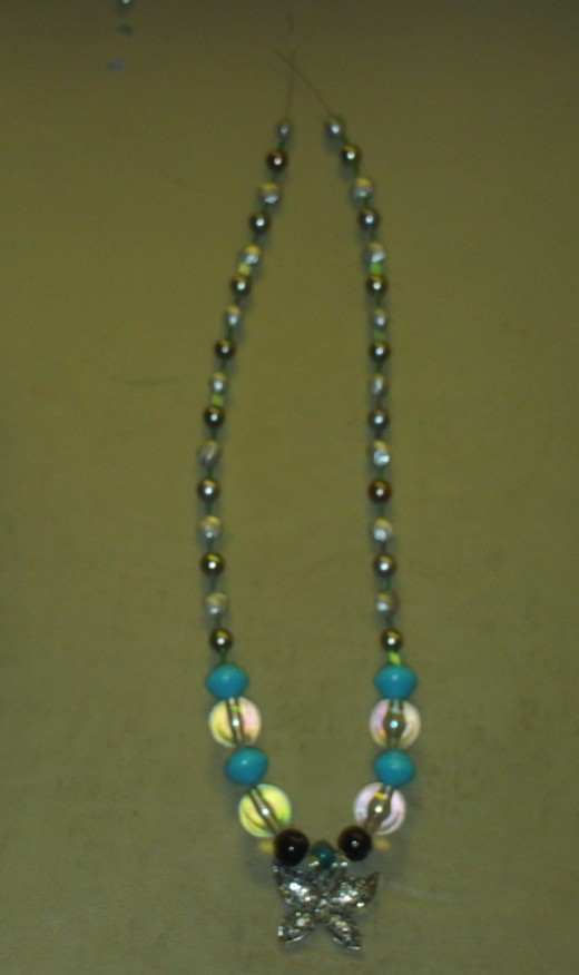 Once all the beads were added to both sides of the necklace I attached the clasp to each side using jewelry pliers.