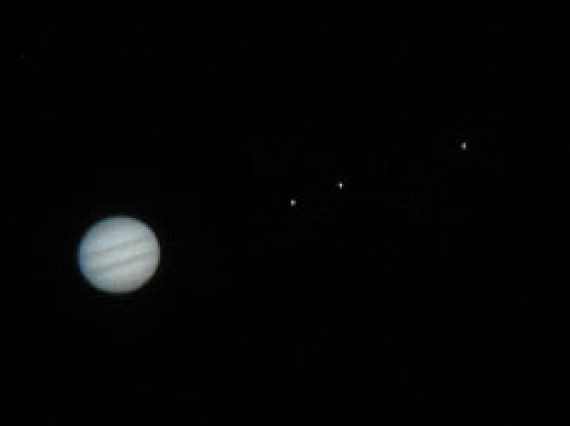 The planet Jupiter as viewed through a small telescope. Notice tiny pinpoints of light to the right of its disk. These are three of the galilean satellites or moons.
