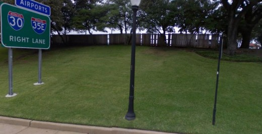 The grassy knoll from the street. A wood fence runs across the top of the small hill. Some witnesses thought shots came from this area. A polaroid photo taken from across the street showed a shadowy figure beneath the trees that wasn't there later.