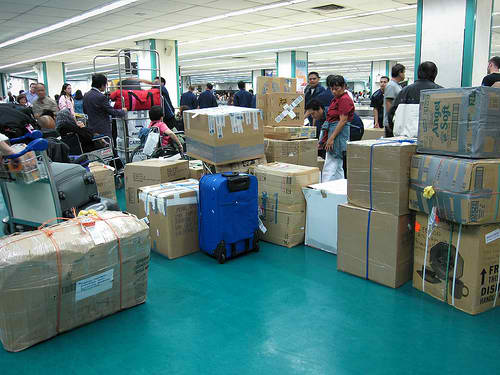 Filipinos with Balikbayan boxes at the airport lounge