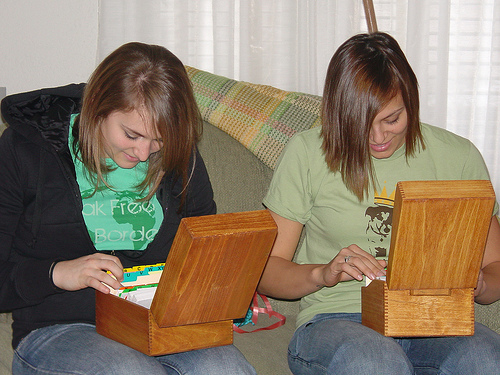 Two young ladies looking at their recipe card files.