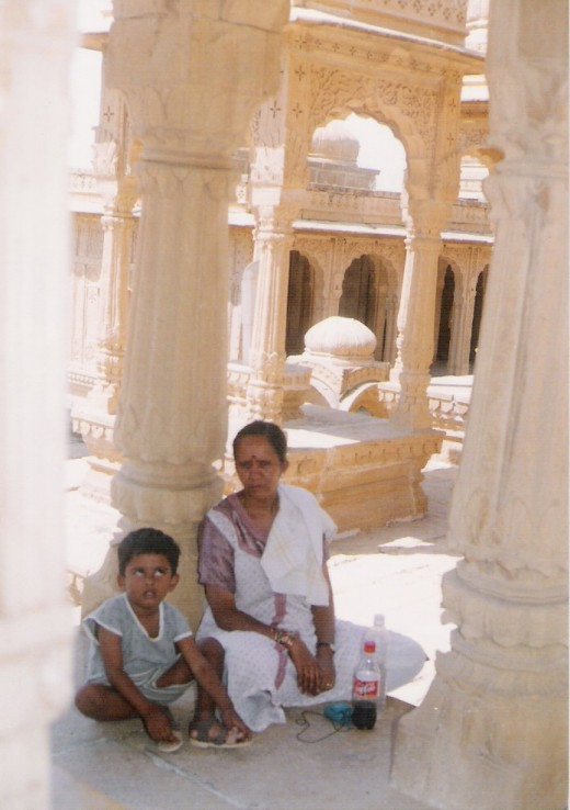 CLOSER VIEW OF JOUHAR TOMBS,BARA BAGH, JAISALMER.(observe the artistic features.Observe closely the tomb behind the visitors has a rounded central platform on which a stone is standing.)