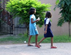 Two girls chat as they speed for the class to start.Their parents must have carried the bags earlier.
