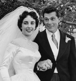 Liz Taylor First wedding to Conrad Hilton in 1950. The 17 year old bride wore a traditional silk satin and seeded pearl gown.