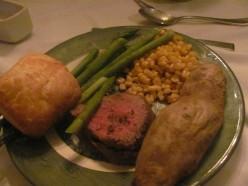 Menu: Beef Tenderloin with parsley sprigs and bearnaise sauce, asparagus, corn, cucumber salad, rolls and baked potatoe