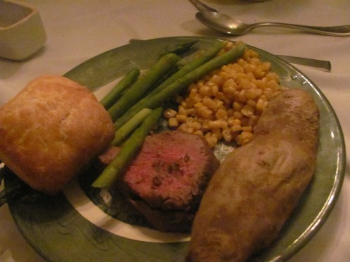 Menu: Beef Tenderloin with parsley sprigs and bearnaise sauce, asparagus, corn, cucumber salad, rolls and baked potatoe