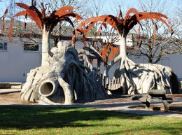 Playground art formed by steel tree tops and concrete sculptured tree stump slide and swinging bridge.