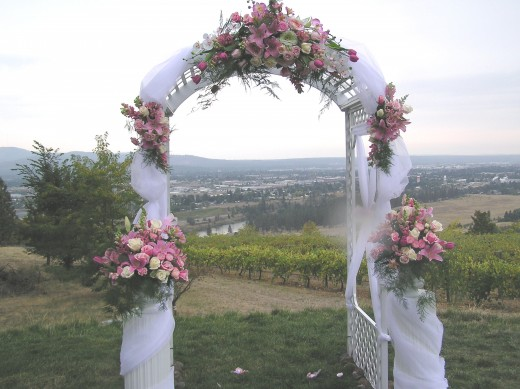 A very feminine arch of pastel flowers and tulle. Tulle and/or sheer fabric helps to soften the arch.
