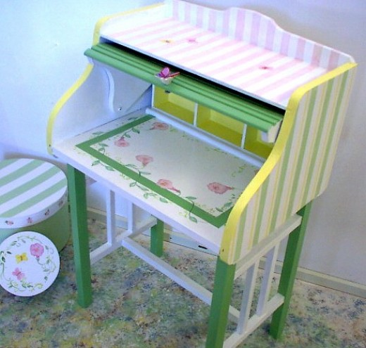 Child's roll top desk with pink butterflies, sripes and flowers.