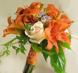 Both a butterfly and a rhinestone buckle add sparkle to this orange lily bouquet.