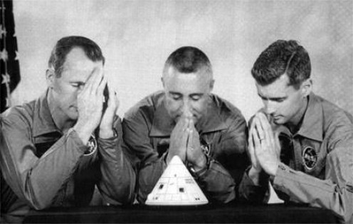 The astronaut team prayed over a model of the Apollo I, having voiced vital concerns about fire hazards. They did, in fact, perish in a fire inside the capsule, suffocating because the hatch locked from the outside. They could not be reached in time.