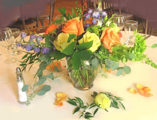 Rose buds and foliage spill around the centerpiece.