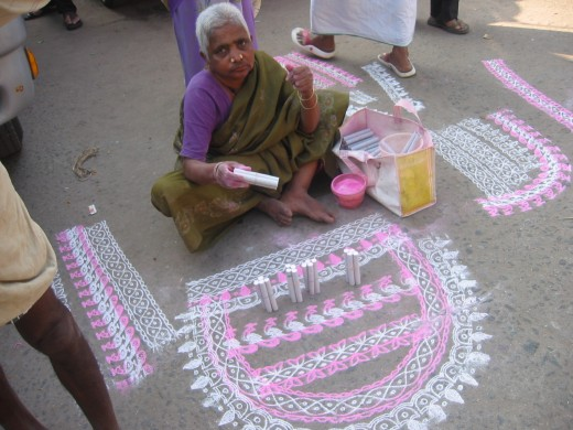 The ladies draw chalk designs outside their houses
