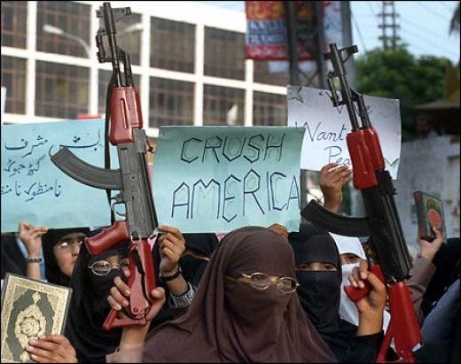 """Muslim waiving the Koran and """"Crush America"""" sign."""