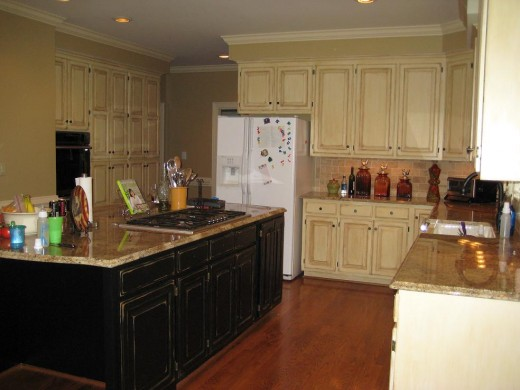 Cream based with mocha glaze on surrounding cabinets.  Island black based with almond distressing