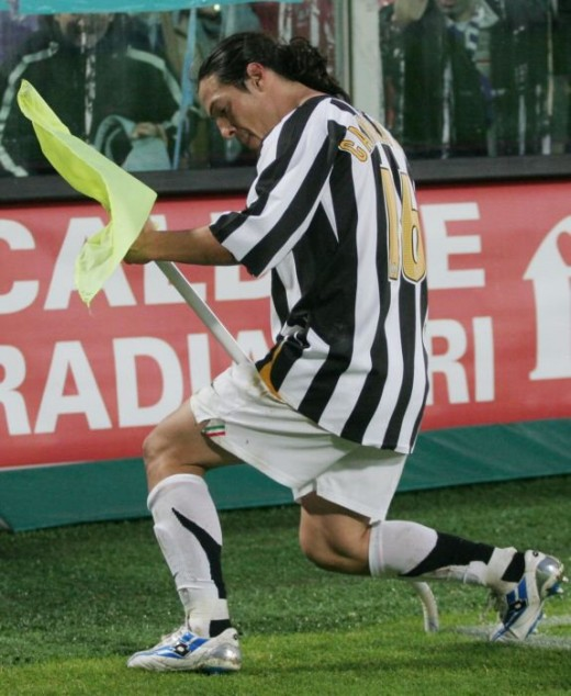 "Argentinian-Italian midfield player, Camoranesi celebrates a goal ""playing"" the corner flag."