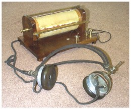 A simple crystal radio, made up of a store bought tuning coil, a crystal, a cat's hair detector wire, and a pair of headphones