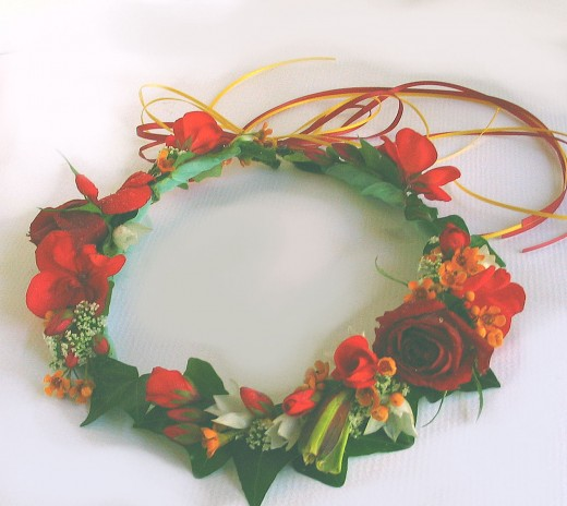 Geraniums are quite hardy. We dotted a few red blossom around this wreath with orange wax flower.