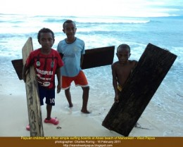 Papuan children with very simple wooden surf boards