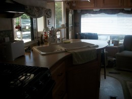 Rear lounge layout - a large picture window at the end of the RV and two overstuffed rocking chairs separated by an end table.