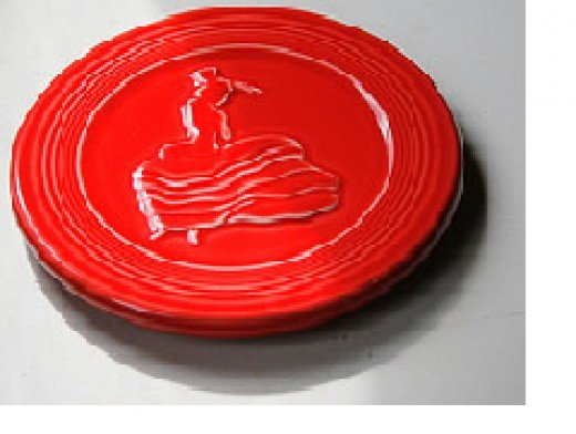 """The famous """"Dancing Lady"""", this one on a scarlet trivet. Sometimes a stamp of the Dancing Lady is another identifyer."""