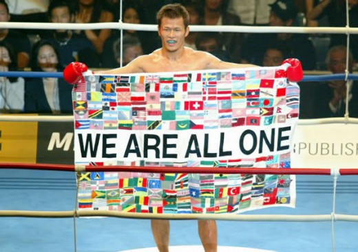 "This is Genki Sudo. A Japanese, former mixed-martial arts fighter, Brazilian Jiu-Jitsu blackbelt, and philosopher. He famously would end every fight by holding up a banner that stated ""We Are All One"", and had many different countries flags on it."