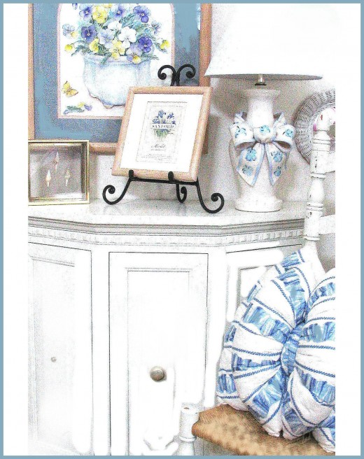 Old Cabinet painted white and placed in the entry with a chair and a few accessories.