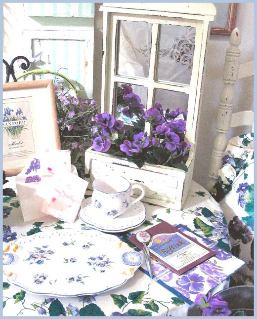 A small round table with purple violets provides a place for business cards, fliers.