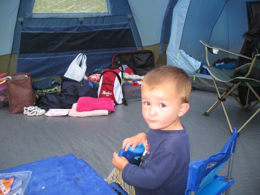 My youngest son, sitting in the centre of the lounge area.  This is the best photo I have of the inside, sorry.  If I had known that one day I would be writing a hub about the tent, I would have been sure to take more photos.