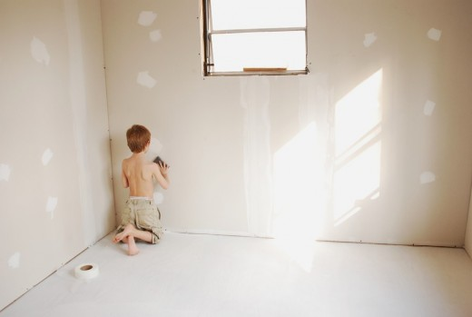 Our youngest son sands drywall in his new room.