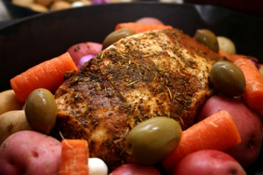 pork roast and vegetables arranged in a cast iron pan and  ready to be grilled