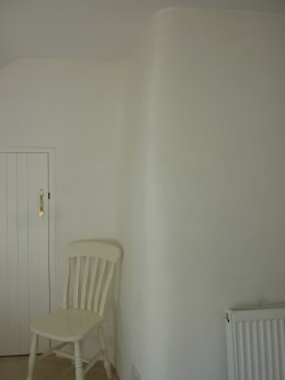 The curve of the chimney breast in a bedroom.