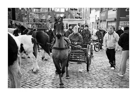 Horse and trap: A teenager is pulled over the cobbles at the Smithfield fare by a horse