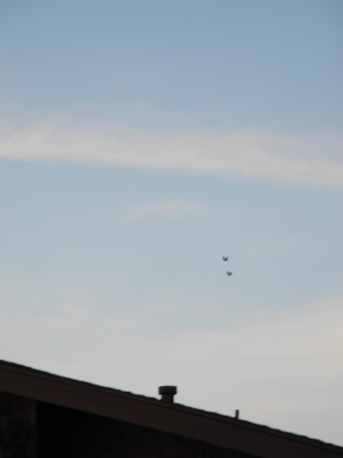 2 Distant Helicopters pan the sky after clouds are beginning to disperse.