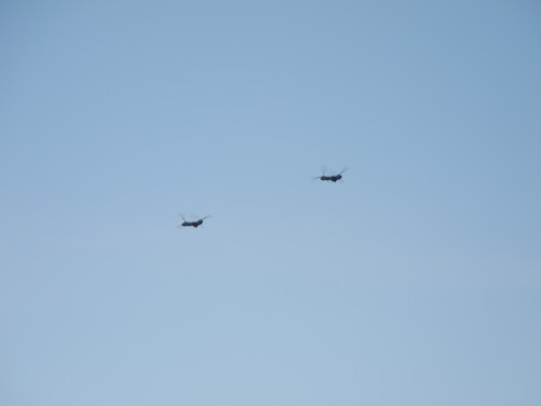 A Pair of Helicopters flying overhead.