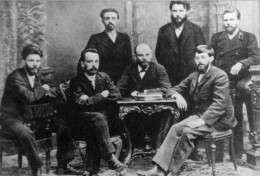 """V.I. Ulianov (Lenin) between the members of the Union of the Fight by the Liberation of the Working Class in Saint Petersburg. """" left to right (standing up): A.L. Malchenko, P.K. Zaporozhets, A.A. Vaneev, of left to right (seated): V.V. Starkov, G.M"""