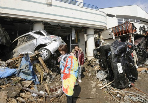 Survivors walk through the debris left after the earthquake that hit Japan March 11, 2011