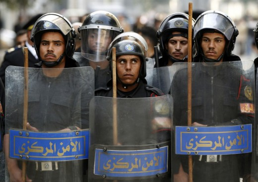 Riot police keep watch as they hold shields during clashes with protesters in Cairo January 26, 2011