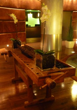 A wooden press utilized as a table in the lobby of the Magnolia Hotel.