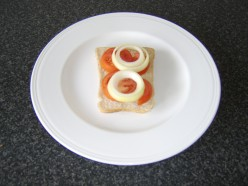 Tomato and onion slices are placed on the bread