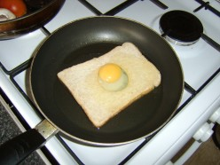 Egg is carefully poured on top of bread to ensure yolk slips in to the hole