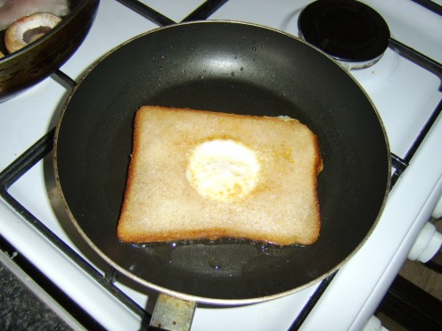 Eggy bread turned over in frying pan