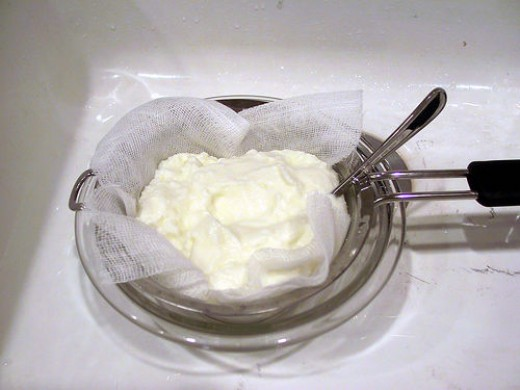 Straining yogurt to yield thick, rich Greek-style yogurt