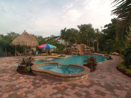 This georgeous pool shows off some great options for your custom in-ground pool.  See the gunite slide, the martini bar with shade umbrella, the brick pavers, and the spa with mosaic waterline tile
