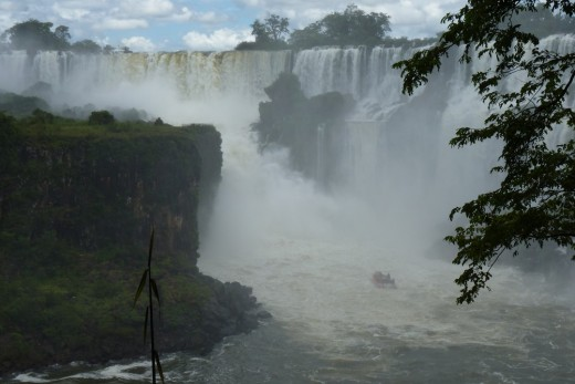 A boat of tourists going into the base of the Devil's Throat at Iguazu Falls on the border of Brazil (left side) and Agrentina (right side)