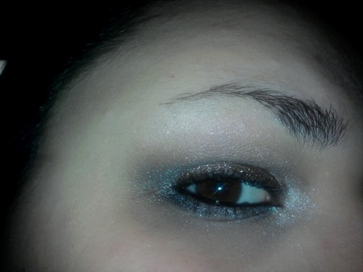 Apply the gun metal gray shadow under the eye and the white shadow into the corner and under the eyebrow, then line the water line with the black eyeliner pencil