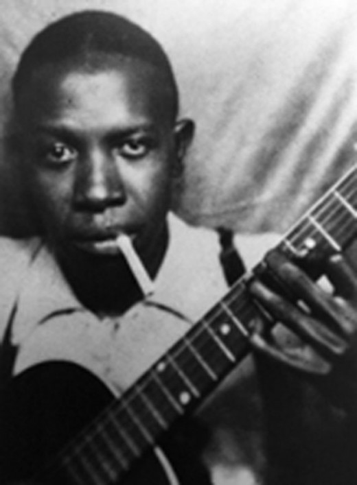 Robert Johnson with guitar in hand. Sadness followed Robert and all his days he spent fleeing the devil.