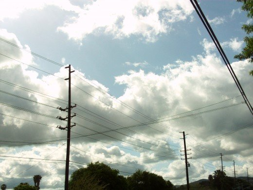Looking up at the telephone poles and the clouds in the sky.
