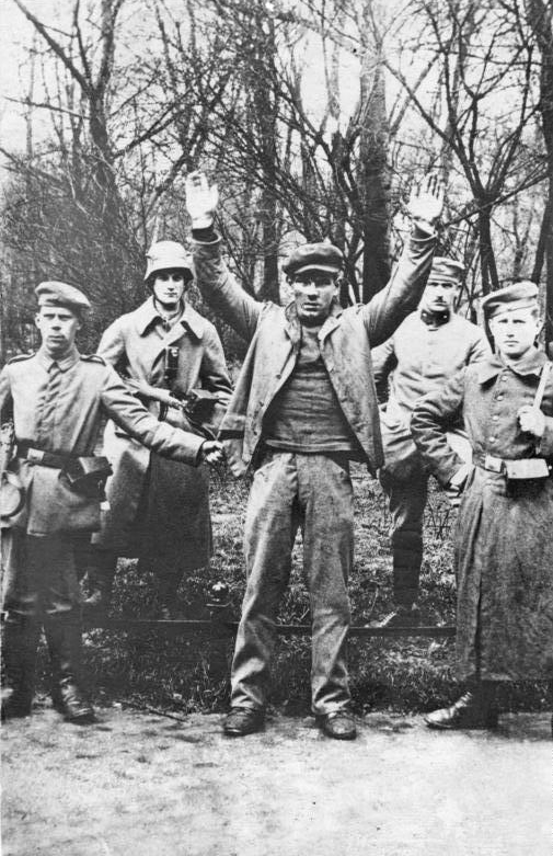 Freikorps posing with a captured revolutionary, May 1919
